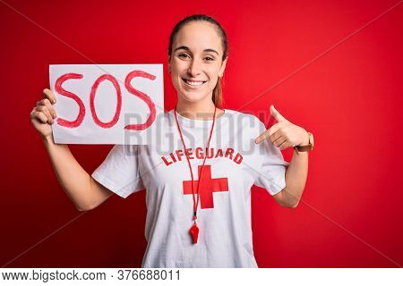 Lifeguard woman wearing t-shirt with red cross and whistle holding banner with sos message with surprise face pointing finger to himself