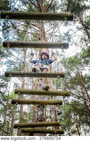 Boy Crossing A Tibetan Bridge In An Adventure Park In A Pine Forest View From Below
