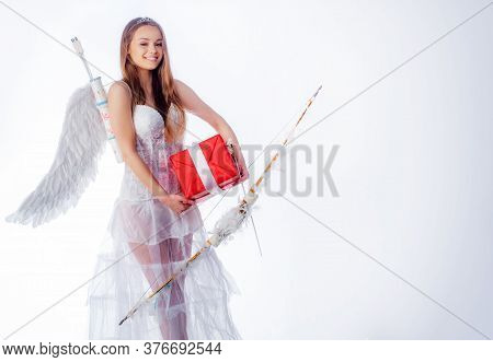 Cute Little Female Cupid Shoots A Bow. Arrow Of Love. Little Goddess With White Wings Alone On Blue