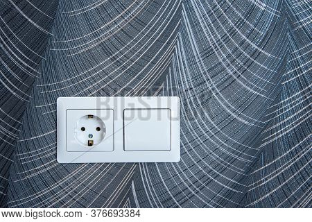 White Plastic Switched Double Socket. Light Switch And Power Socket Control Panel On Abstract Wallpa