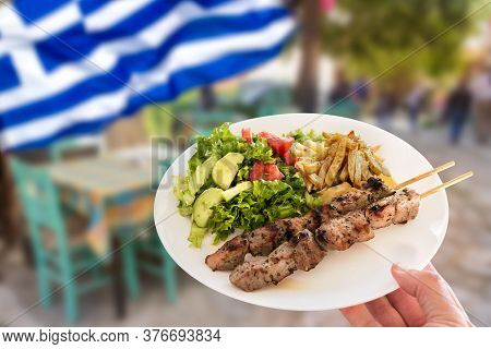 Hand Holding A Traditional Greek Pork Souvlaki Plate With Fried Potatoes And Green Salad. Greek Tour