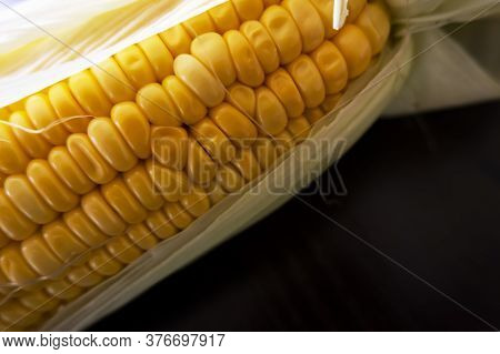 A Macro Shot Of Raw Maize Corns & Leaves On Wooden Table
