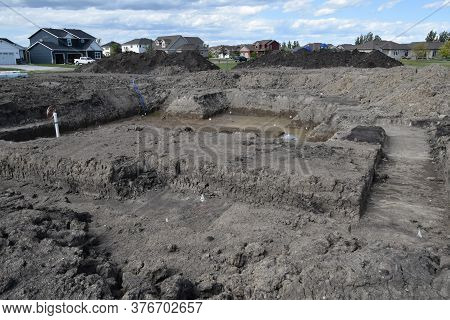 An Excavation Site Hole Shows The Layout Of A New Home Ready To Have Forms And  A Concrete Foundatio