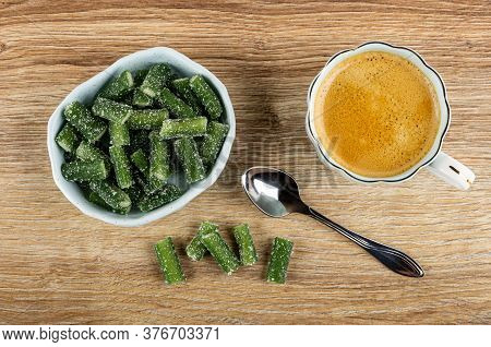 Bowl With Chewing Marmalade In Form Green Bean, Spoon, Few Marmalades, Black Coffee In Cup On Brown