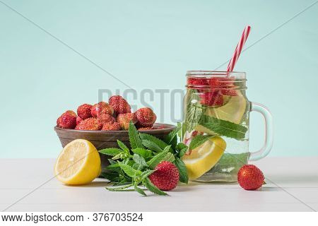 A Refreshing Drink Of Berries, Lemon And Mint And A Bowl Of Strawberries On A White Table. Freshly P