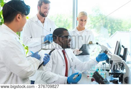 Scientist and students working in lab. Doctor teaching interns to make blood analyzing research. Biotechnology, chemistry, bacteriology, virology and health care concept.