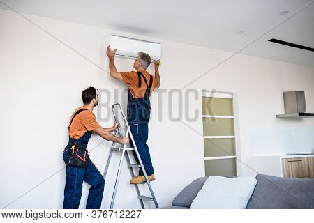 Two Workers In Uniform, Air Conditioning Masters Using Ladder While Installing A New Air Conditioner