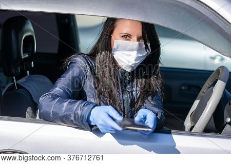 A Girl In A Medical Anti-bacterial, Anti-virus Mask And Rubber Gloves Sits Behind The Wheel Of A Car