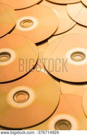 CDs and DVDs in golden tone as background. Soft focus.