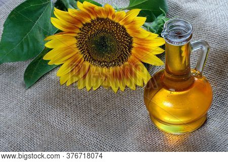 Sunflower Oil And A Sunflower Flower On The Table. Natural Vegetable Oil. Copy Space
