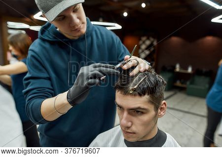 Professional Male Barber Making New Trendy Haircut For A Young Handsome Guy Sitting In Barbershop Ch