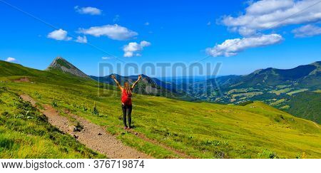 back view of backpacker tourist girl on the mountain in France, Cantal