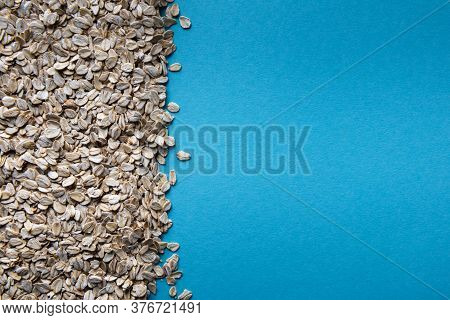 Background With Natural Dry Rolled Oats And With Large Square Copy Space On Blue Paper Texture. Sour