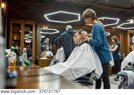 Visiting Barbershop. Side View Of A Professional Barber Girl Making New Modern Haircut For Young Han