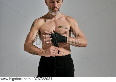 Cropped Shot Of Half Naked Middle Aged Athletic Man, Kickboxer Wrapping Hands For Muay Thai Boxing O