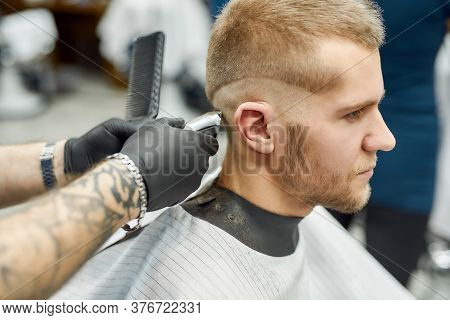 Close Up Shot Of A Young Handsome Caucasian Man Getting Haircut, Visiting Barbershop. Barber Using P