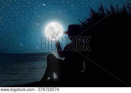 forces a girl who meditates at sunset on the sea.  Elements of this image furnished by NASA