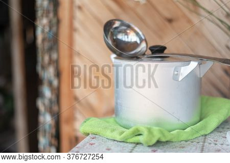 Casserole And Ladle On The Rural Table Background.