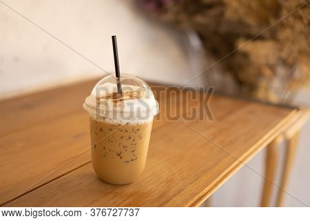 Tasty Drinking, A Cup Of Ice Cappuccino Coffee Decorated With White Milk Froth In A Tall Plastic Gla