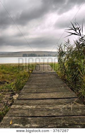 Wooden Jetty On Over The  Beach With Grey Sky And Clouds