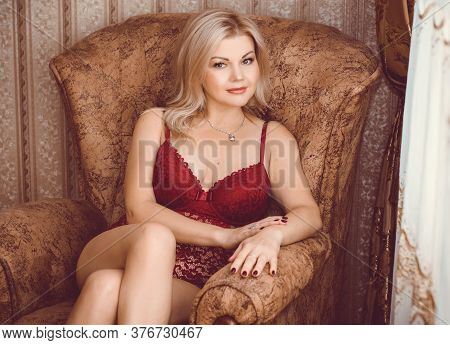 Seductive Sexy Gorgeous Middle Age Woman Wearing Lingerie In Armchair At Home. Attractive Sensual La