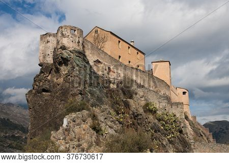 Panoramic view of the citadel perched high on a rock hilltop with dramatic cloudy sky in Corte, Corsica, France