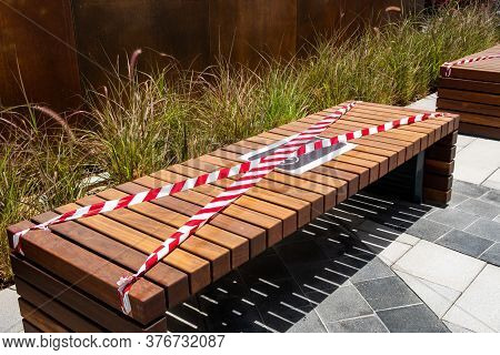 Wooden Brown Bench With 'no Sitting' Sign In English And Arabic And Red And White Barricade Tape, Sa