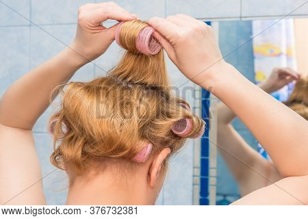 A Middle-aged Woman Of European Appearance Winds Curlers On Her Hair At Home In The Bathroom.