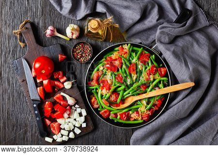 Caribbean Stir-fried Green Beans With Onions And Tomatoes, Fry Bodi In A Skillet On A Wooden Table W