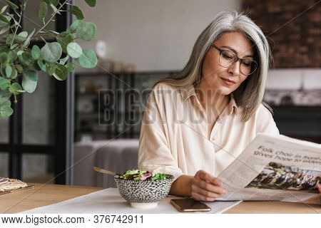 Image of mature concentrated woman indoors at home reading newspaper