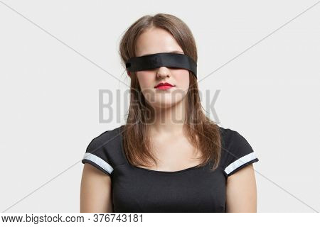 Young blindfolded woman against gray background