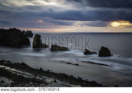 Long Exposure Over Calm Sea With Rocks During A Cloudy Sunset With Copy Space