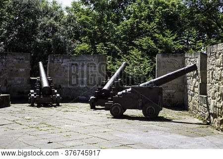 Three Cannons On Ancient Defensive Wall With Green Trees Background With Copy Space