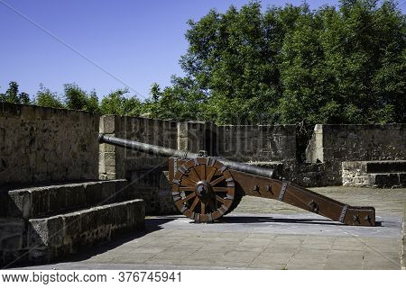 One Cannon On Ancient Defensive Wall With Green Trees Background With Copy Space