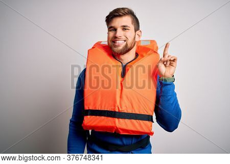 Young blond tourist man with beard and blue eyes wearing lifejacket over white background showing and pointing up with finger number one while smiling confident and happy.