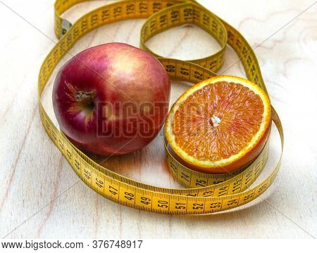 Collage Of Apple, Orange And Centimeter Located On A Brown Background. A Fruit Diet Will Help You Lo