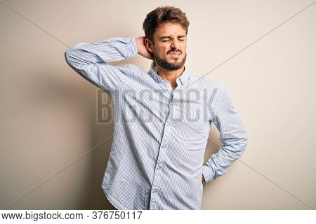 Young handsome man with beard wearing striped shirt standing over white background Suffering of neck ache injury, touching neck with hand, muscular pain