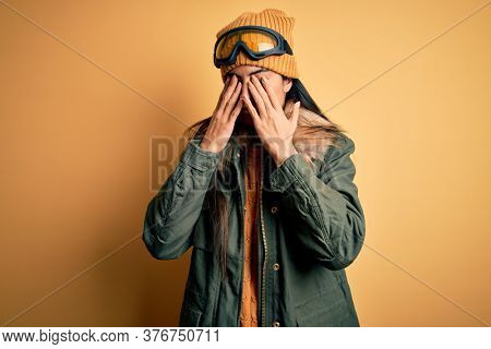 Young beautiful hispanic woman wearing ski glasses and coat for winter weather rubbing eyes for fatigue and headache, sleepy and tired expression. Vision problem