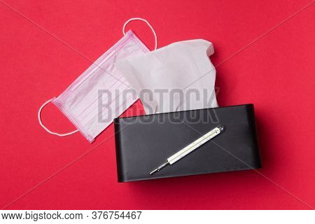 Pink Medical Facemask, Mercury Thermometer And Box With Napkins On Red Background.