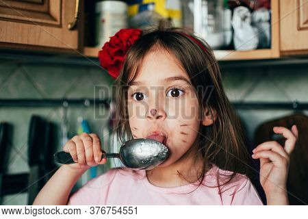 Cute Toddler Girl With Face Painting Like A Cat, Licking Spoon With Honey In The Kitchen. Real Life