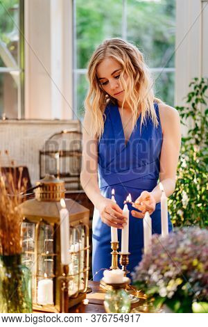 The Girl In The Blue Dress Lit Candles With A Match. Decoration Decor Or A Romantic Dinner.