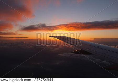 Spectacular Sunset From Inside An Airplane Over Clouds A Valley And A River With The Left Plane Wing