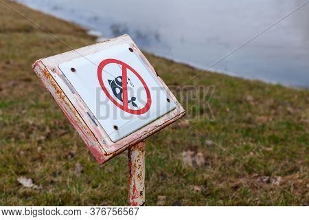 Fishing Is Not Allowed Here, Caution Sign On Lake Coast, Close-up Photo With Selective Focus