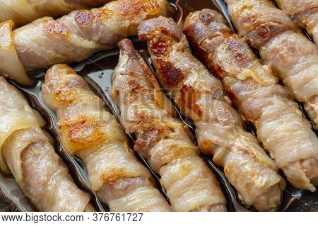 Cooked Sausages In Bacon. Bacon Roll Close Up. Abstract Background With Bacon.