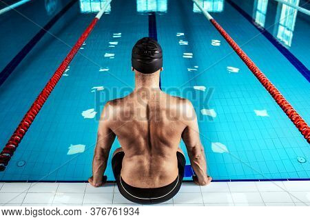 Swimmer Sitting At The Poolside, Back View. Professional Swimmer Near The Swimming Pool, Hard Contra