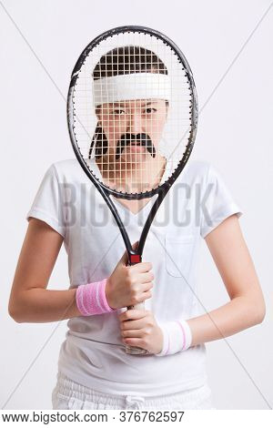 Portrait of young woman with a fake mustache holding tennis racket in front of her face against white background