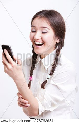 Cheerful young woman reading text message on her cell phone against white background