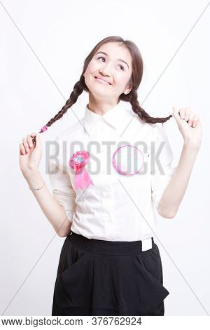 Young woman with pigtails daydreaming against white background