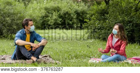 Couple Have Date During The Coronavirus Lockdown Crisis. Man And Woman In The Park. Social Distancin