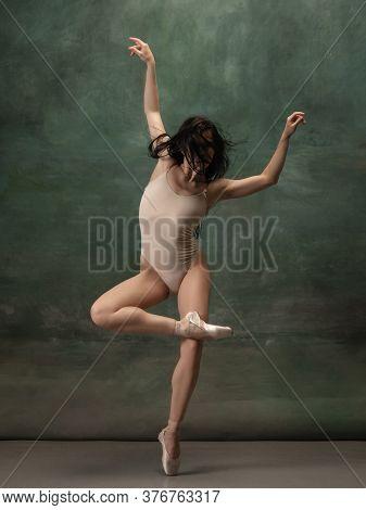 Inspiration. Graceful Classic Ballerina Dancing On Dark Studio Background. Pastel Bodysuit. The Grac